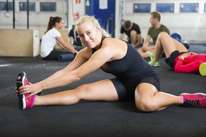 Confident Female Athlete Doing Stretching Exercise At Health Club
