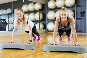 Confident Female Friends Doing Pushups In Gym
