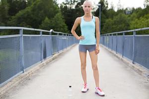 Confident female runner having her break after running