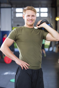 Confident Fit Male Athlete Holding Kettlebell In Health Club