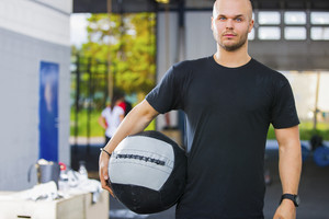 Confident Male Athlete Holding Medicine Ball In Health Club