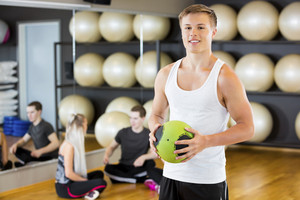 Confident Man Holding Medicine Ball While Friends Resting In Gym
