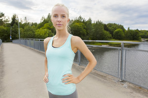 Confident woman stands at bridge after workout