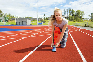 Confident Woman Tying Shoe Lace On Running Tracks