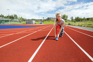 Confident Woman Tying Shoelace On Running Tracks