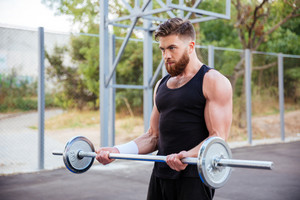 Confident young bearded fitness man doing exercises with barbell outdoors