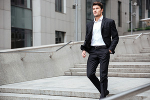 Confident young businessman in suit walking outdoors