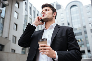 Confident young businessman with take away coffee talking on cell phone near business center