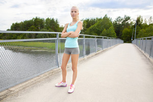 Confident young female runner stands at bridge