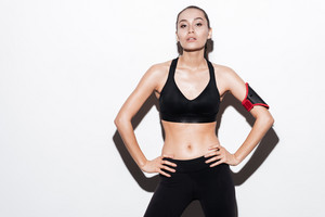 Confident young fitness woman with armband in black sportswear over white background