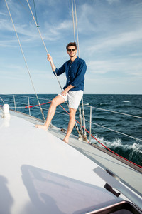 Confident young man looking forward and smiling while standing on the yacht