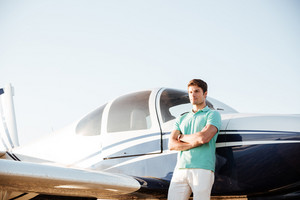 Confident young man standing with arms crossed in front of small airplane