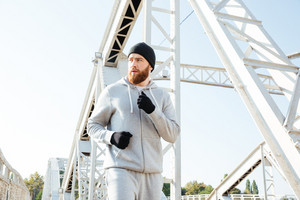 Confident young sports man athlete running outdoors across the bridge