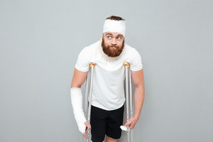 Confused bearded young man standing with crutches over white background
