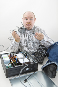 Confused Businessman Holding Tangled Cables Of Computer At Desk