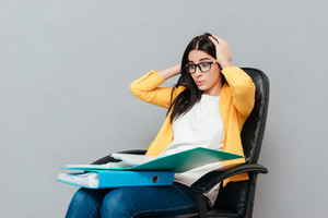 Confused woman wearing eyeglasses and dressed in yellow jacket holding folders while sitting on office chair and looking at folders over grey background.