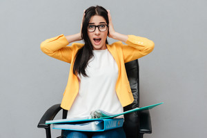 Confused woman wearing eyeglasses holding folders while sitting on office chair and looking at camera over grey background.