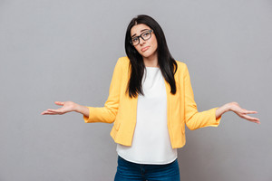 Confused young woman dressed in yellow jacket over grey background. Look at camera.