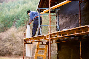 Construction worker standing on scaffold thermally insulating house facade, putting black foil on