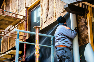 Construction worker standing on scaffold thermally insulating house facade with glass wool and black foil.