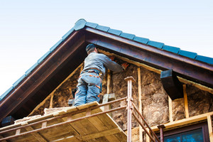 Construction worker standing on scaffold thermally insulating house facade with glass wool.