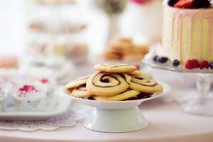 Cookies in shape of spiral, cake with berries and cupcakes laid on table with pink tablecloth and handmade lace. Studio shot.
