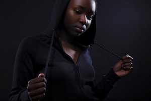 Cool and pensive woman with dark skin and attitude wearing hoodie