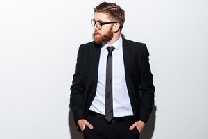 Cool bearded business man in glasses and black suit standing with arms in pockets and looking aside. Isolated gray background
