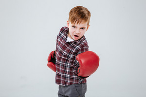 Cool little boy in red boxing gloves standing and training over white background
