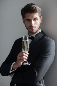Cool model with champagne. in suit. gray background