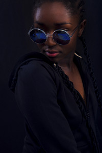 Cool young woman with dark skin wearing round sunglasses