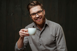 Cose up portrait of a happy smiling man in eyeglasses holding cup and looking at camera isolated on a black wooden background