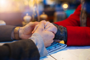 Couple in love in cafe, holding each other's hand. Closeup of hands