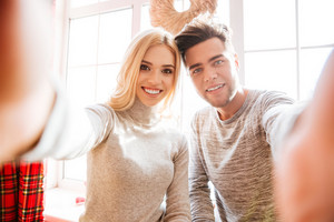 Couple in sweaters makes selfie in house.
