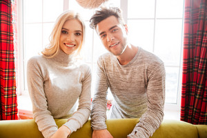 Couple in sweaters near the sofa in house. looks at camera