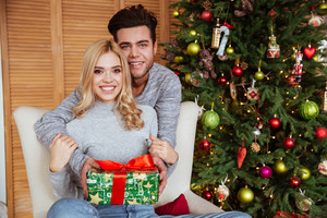 Couple in sweaters with gift near the fir-tree looks at camera. girl sitting on chair