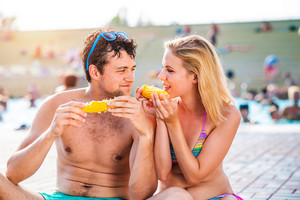Couple in swimming suits at the crowded pool eating corn outside in sunny summer aquapark