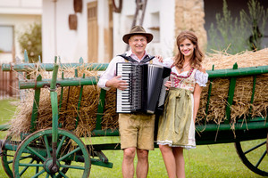 Couple in traditional bavarian clothes standing in front of wooden cart with dried hay. Man playing accordion. Oktoberfest.