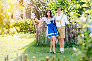 Couple in traditional bavarian clothes standing in the garden in front of wooden fence. Oktoberfest.