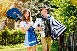 Couple in traditional bavarian clothes standing in the garden in front of wooden fence, playing accordion, holding guitar. Oktoberfest.