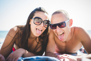couple lying on beach toowl in summertime using smartphone showing tongue piercing