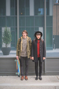 Couple of beautiful woman and man, with moustache and skate, posing on a wall in the city - freshness, youth, carefreeness concept