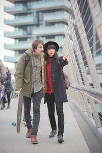 Couple of beautiful woman and man, with moustache and skate,walking through the streets of the city hugging and chatting- freshness, youth, carefreeness concept