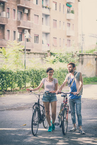 couple of friends young  man and woman riding bike in the city