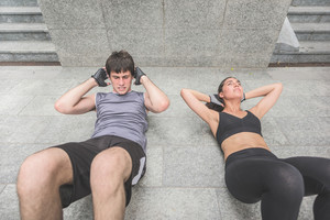 Couple of handsome caucasian sportive man and woman doing abdominal lying on the floor - sportive, healthy, training, practice, fitness concept