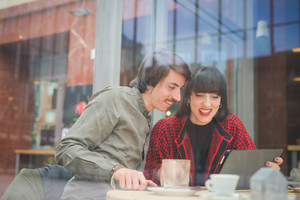 Couple of young beautiful caucasian man and woman business colleague seated on a bar using tablet and smartphone - technology, business, communication concept