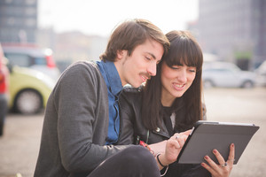 Couple of young beautiful caucasian man and woman business colleague seated on a sidewalk in the city using a tablet - business, technology, communication concept