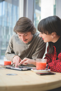 Couple of young beautiful caucasian man and woman business collegue seated on a bar using tablet and smartphone - technology, business, communication concept