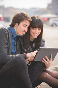 Couple of young beautiful caucasian man and woman business collegue seated on a sidewalk in the city using a tablet - business, technology, communication concept