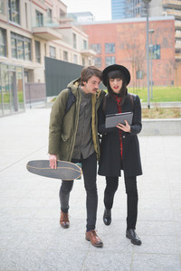 Couple of young beautiful woman and man, with moustache and skate, walking through the city using a tablet - technology, social network, communication concept